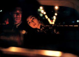 Para w mroku siedząca na tylnych siedzeniach taksówki