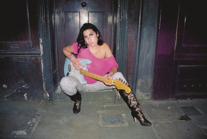 Dziewczyna z gitarą ubrana w różowy sweter, jeansy i kozaki