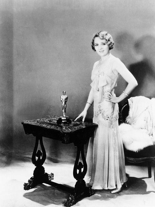 Czarno-biała fotografia kobiety w sukni pozującej z Oscarem