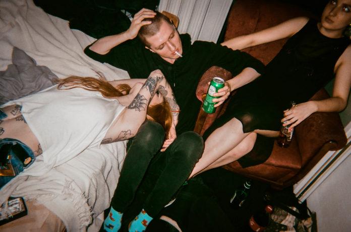 Dziewczyna leżąca na łóżku, chłopak z butelką piwa i dziewczyna na fotelu