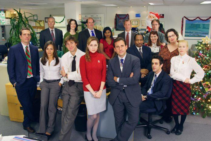 Grupa ludzi z serialu The Office stojąca w biurze