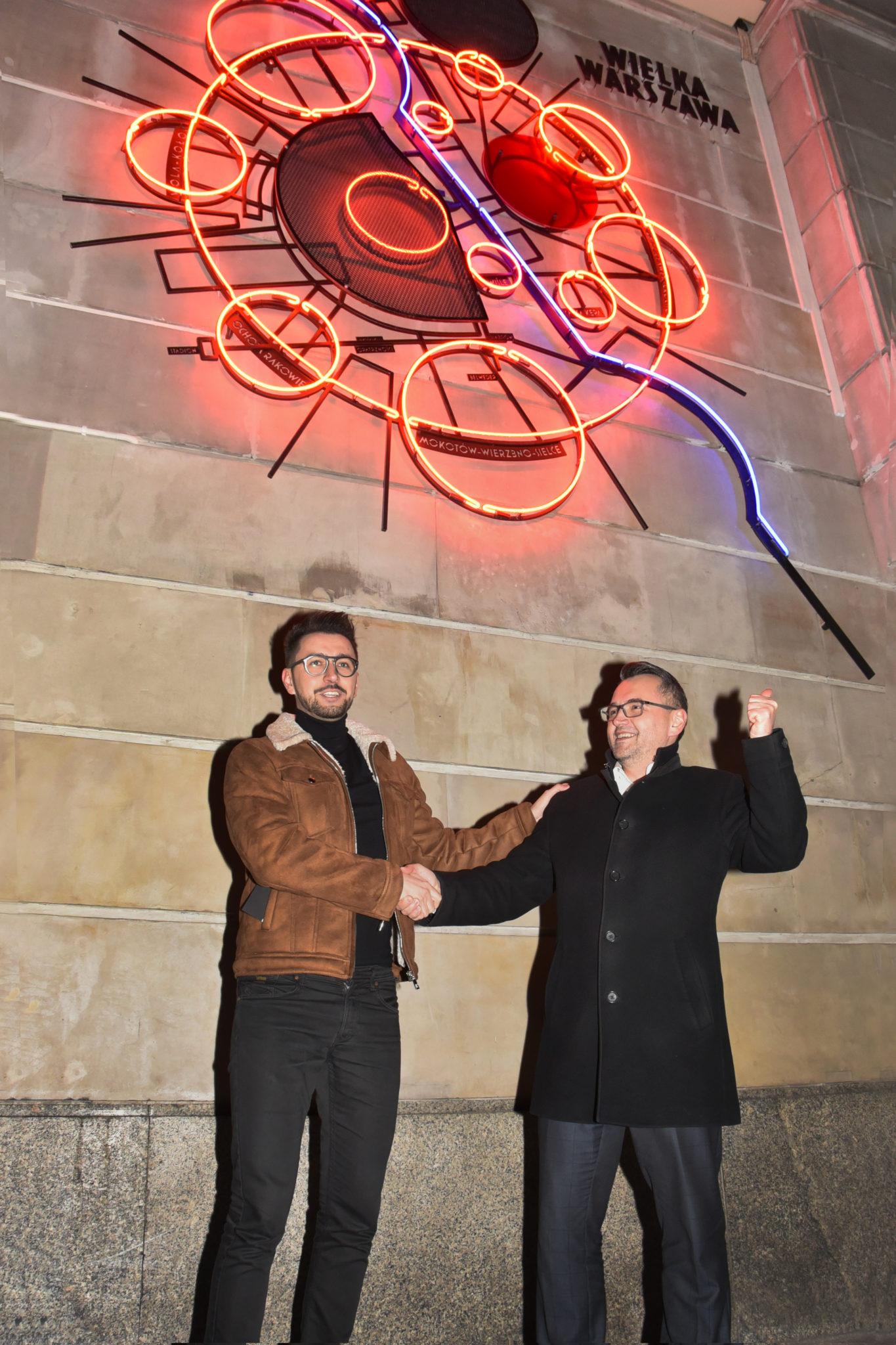 Dwóch mężczyzn stojących pod neonem