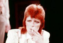 Mężczyzna w rudych włosach palący papierosa