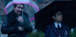 Mężczyzna z różowym parasolem i chłopiec obok z czarnym parasolem