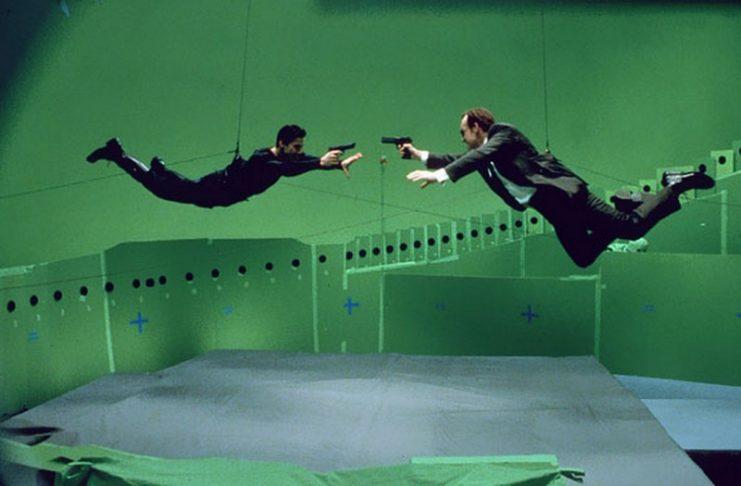 Dwóch mężczyzn zawieszonych na linkach na zielonym tle