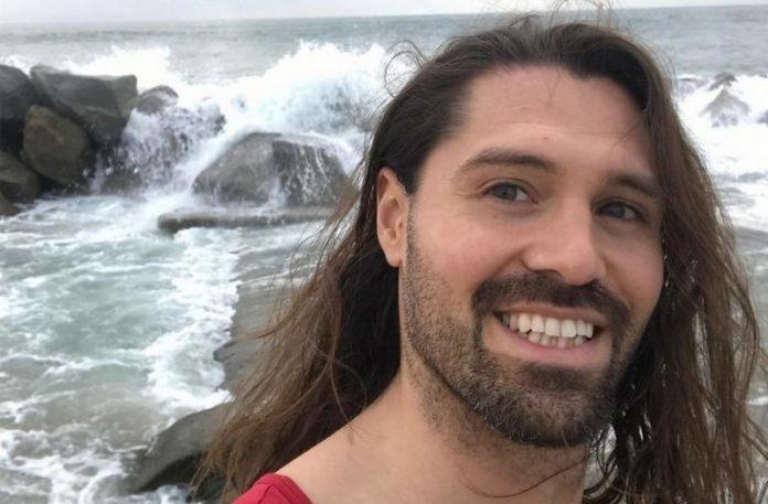 Mężczyzna z długimi włosami na tle morza