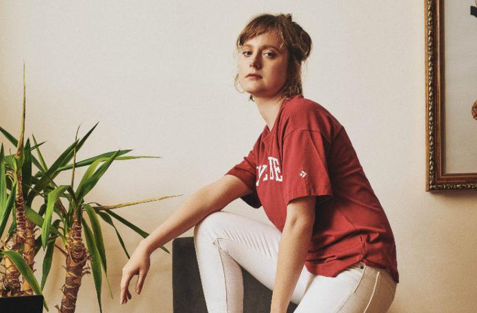 Dziewczyna w czerwonej koszulce i białych spodniach na fotelu