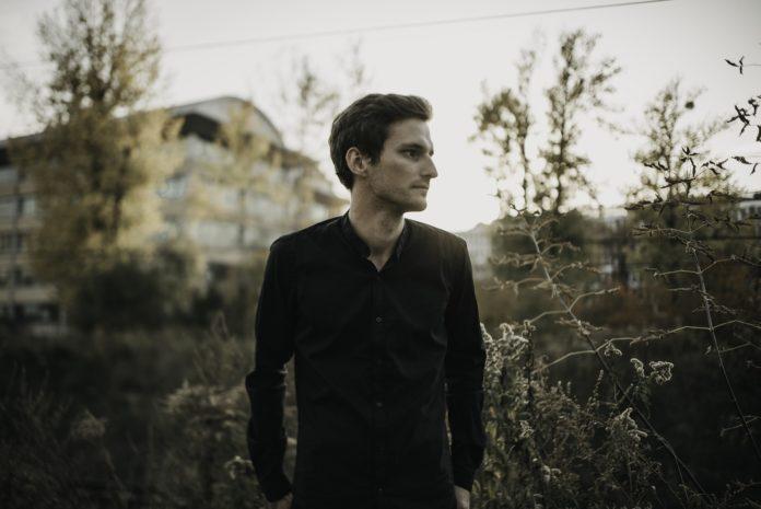 Chłopak w ciemnej bluzce stojący na polanie