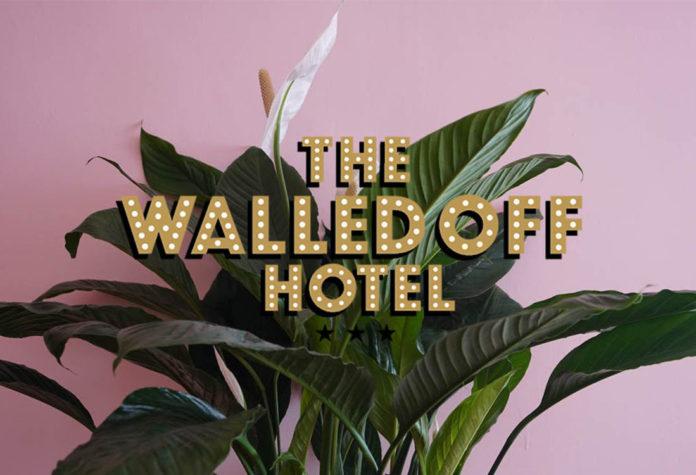 Napis The Walled Off Hotel z rośliną i różowym tłem