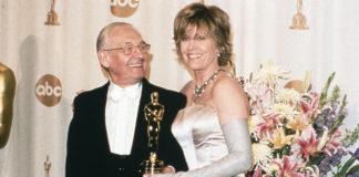 Męzczyzna i kobieta w wieczorowych strojach trzymający Oscara
