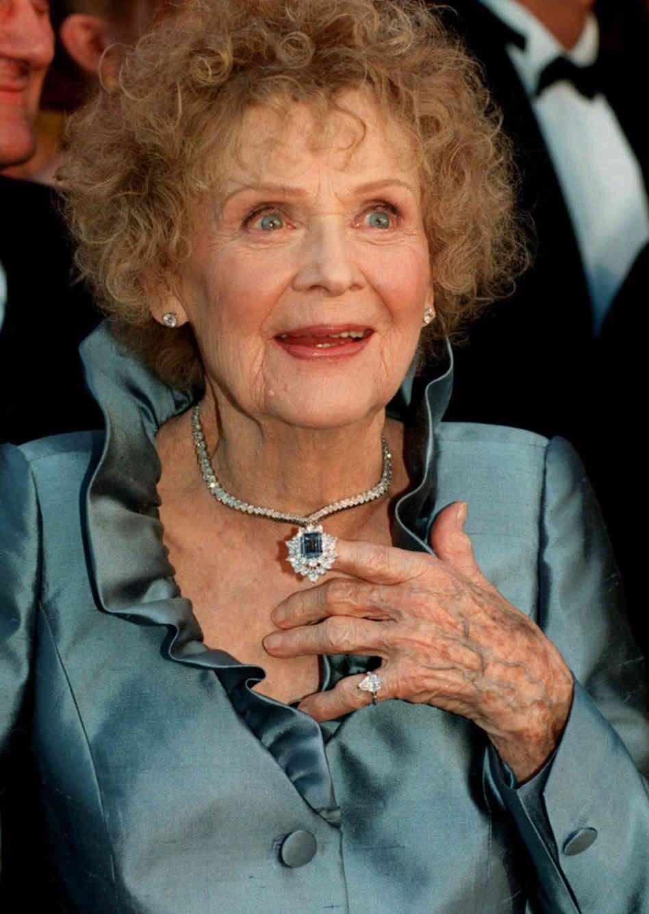 Starsza kobieta w niebieskiej sukience i naszyjniku z niebieskim diamentem