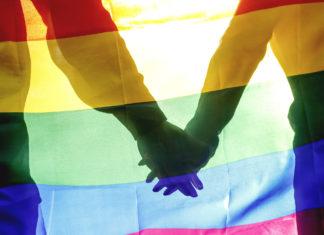 Tęczowa flaga i splecione ręce dwójki ludzi