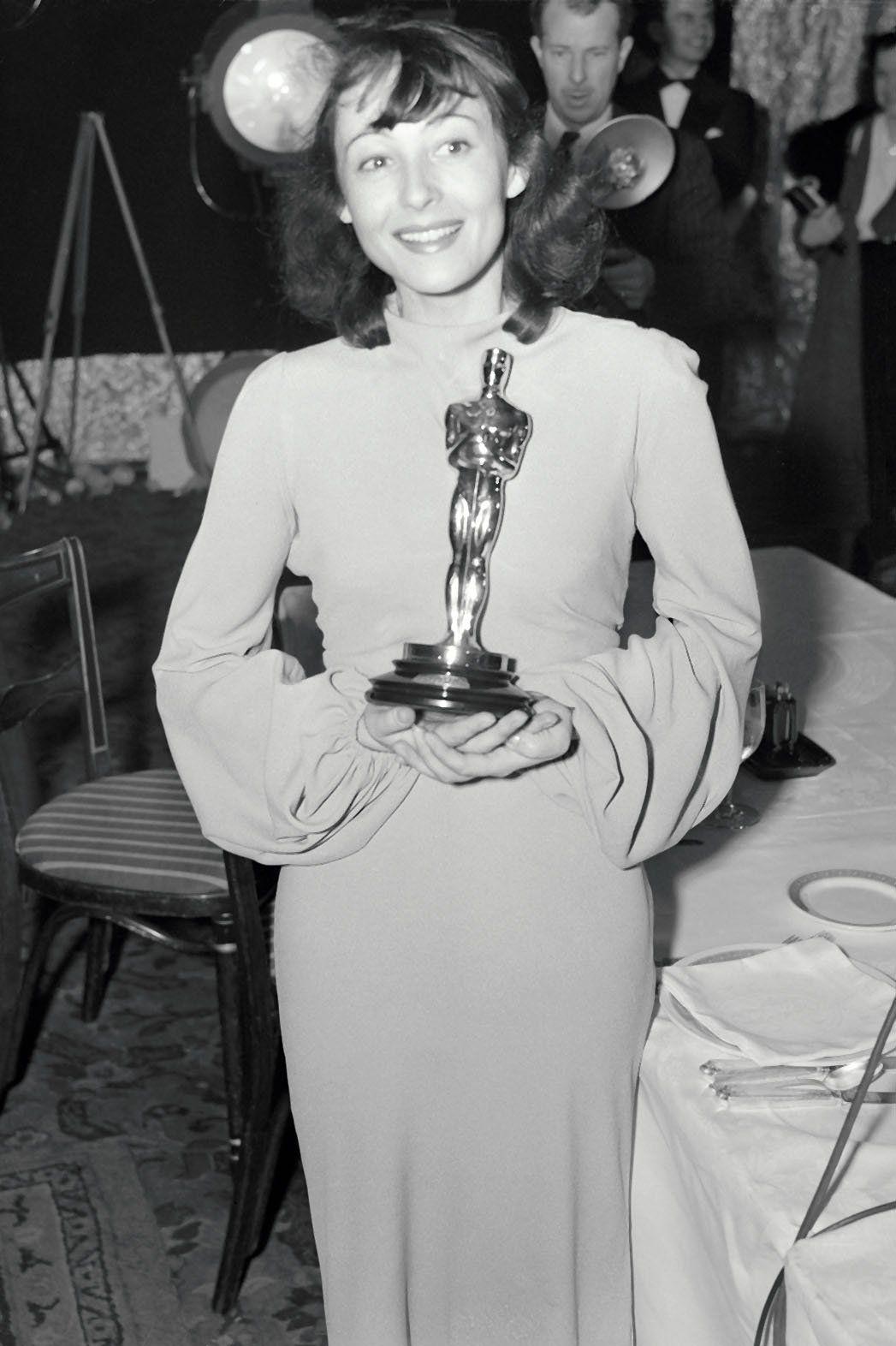Czarno-białe zdjęcie kobiety w sukni pozującej z Oscarem