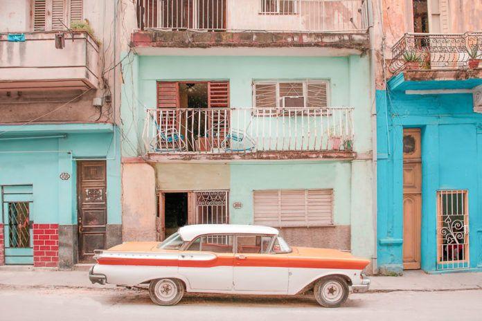 Samochód stojący przed pastelowym budynkiem