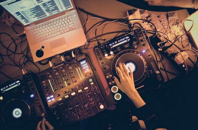Zdjęcie dłoni kobiety przy stanowisku DJskim