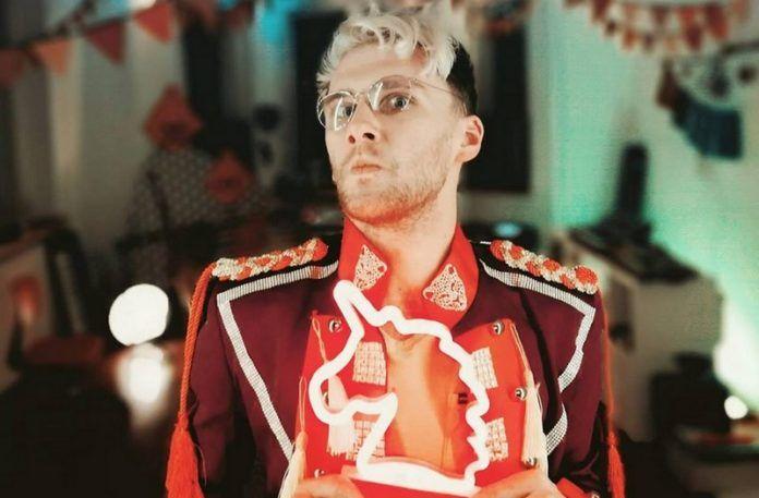 Mężczyzna w czerwonej marynarce z lampą jednorożca w ręku