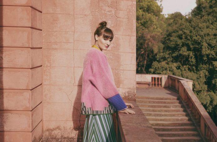 Dziewczyna w różowym swetrze stojąca przy balustradzie na ganku