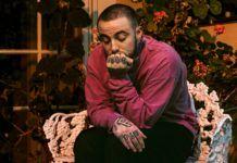 Chłopak w różowej bluzie przyciskający twarz do ręki