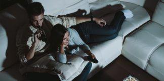 Para oglądająca telewizję na kanapie