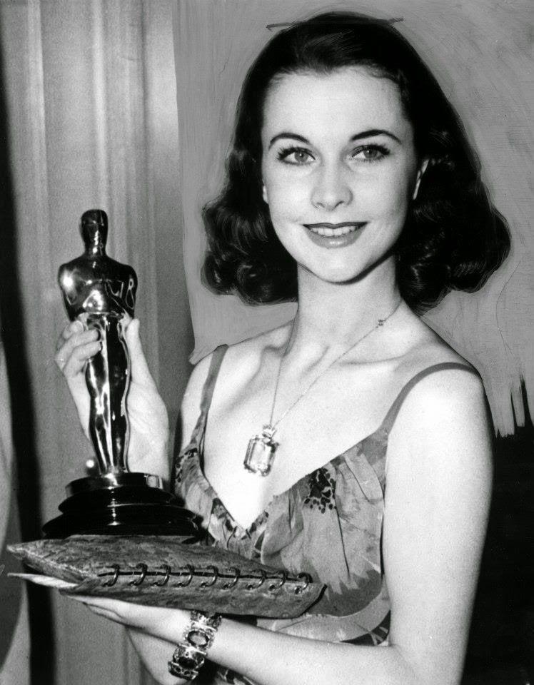 Czarno-białe zdjęcie kobiety w ciemnych włosach z Oscarem w ręku