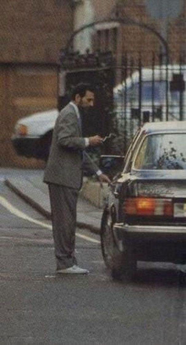 zdjęcie przedstawiające Frediego Mercurego z papierosem w garniturze przy samochodzie