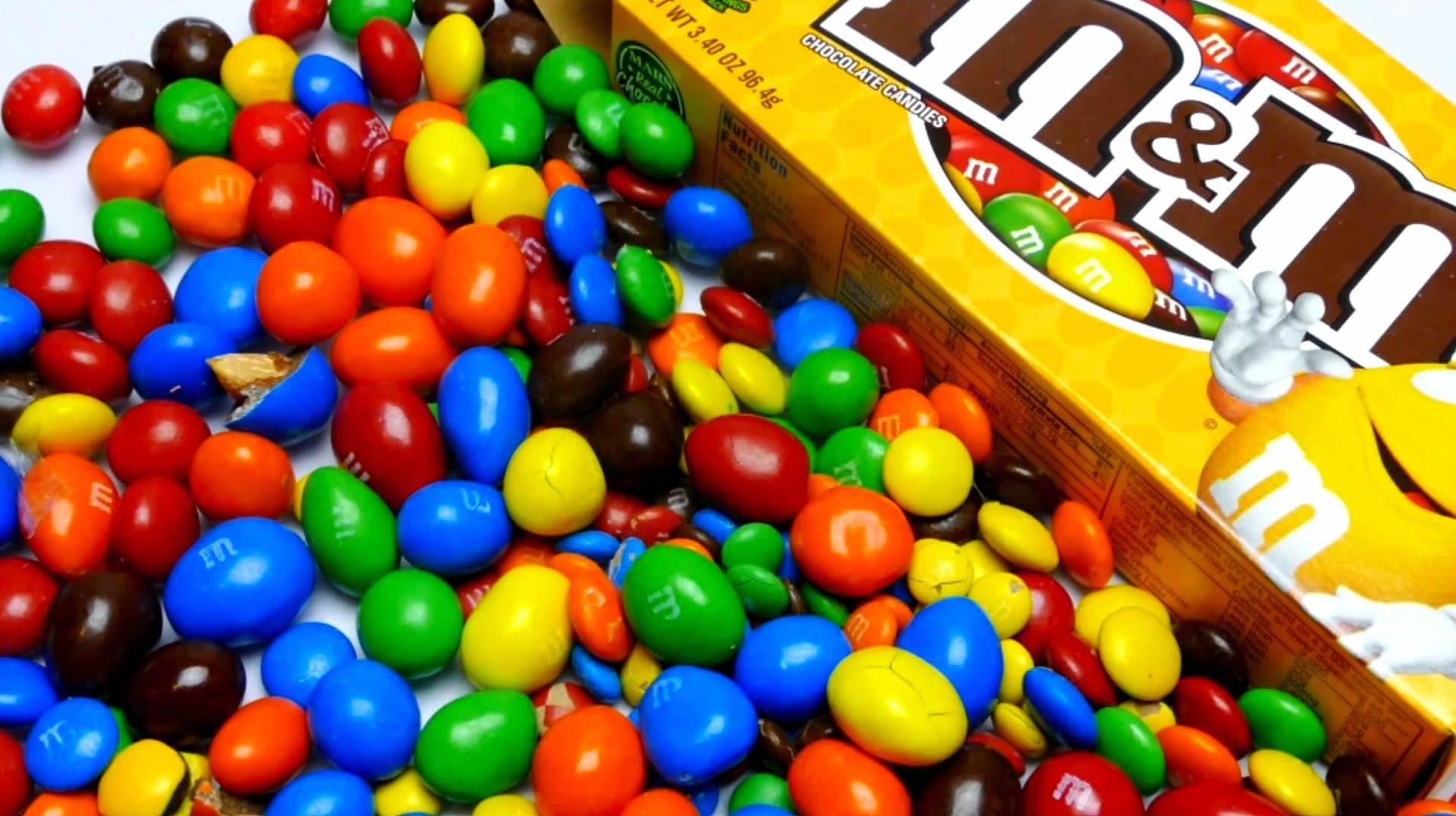 Pudelko cukierkow i rozsypane kolorowe cukierki