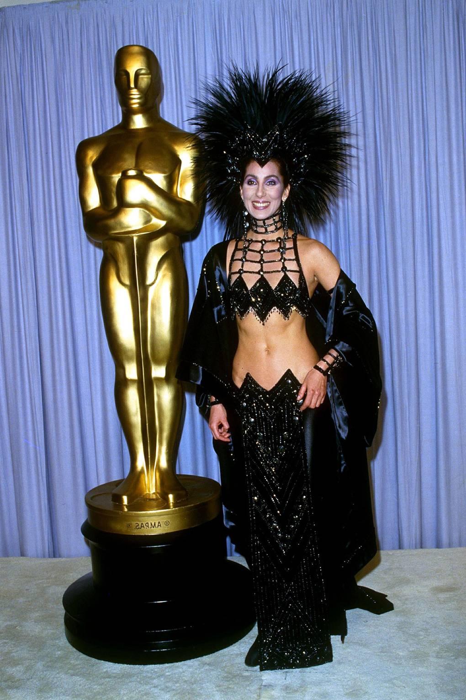 Kobieta w wyzywającym stroju obok statuetki Oscara