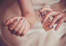 Kobieca dłoń pryskająca nagdarstek perfumami