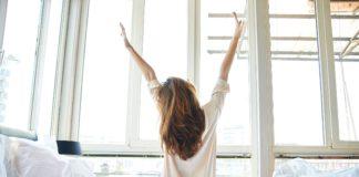 Kobieta siedząca na łóżku w rękami w górze
