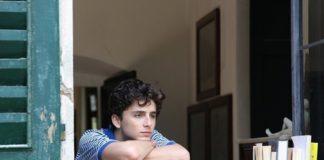 Chłopak wyglądający przez okno, oparty o książki