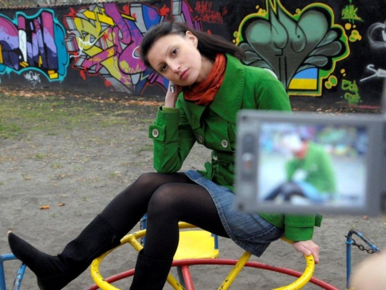 mloda kobieta pozuje przed widocznym obiektywem aparatu na tle kolorowego grafitti