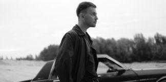Czarno-białe zdjęcie mężczyzny na tle samochodu