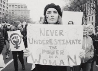 Czarno-białe zdjęcie kobiety z tabliczką