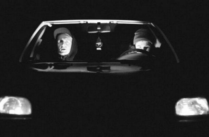 Dwóch mężczyzn w czapkach w czarnym samochodzie