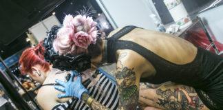 Dziewczyna z kwiatami we włosach tatuująca drugą