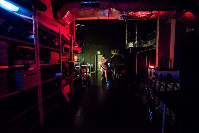 Dziewczyna stojąca w oddali na backstage'u koncertu
