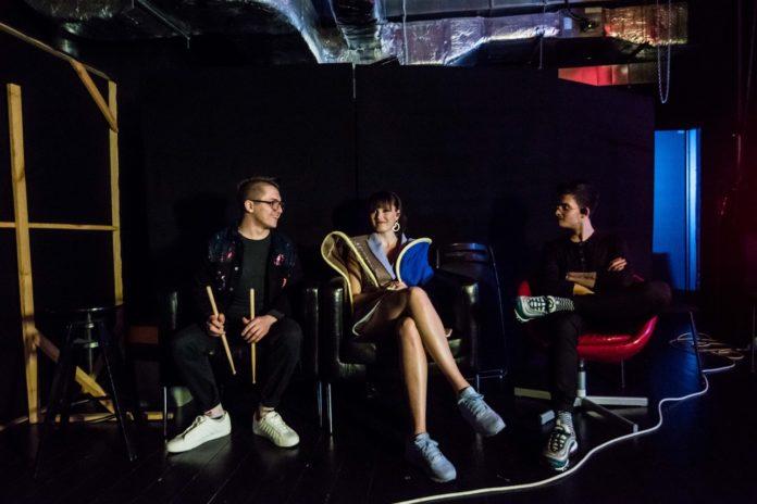 Dziewczyna siedząca na krześle z dwoma chłopakami