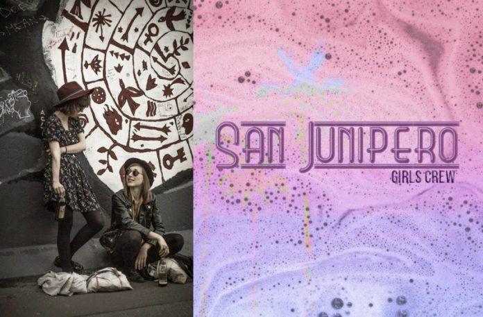 Dwie dziewczyny przy ścianie i logo San Junipero Girls Crew