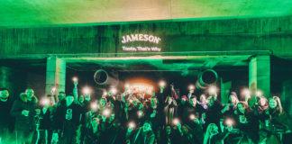 Grupa ludzi pozująca do zdjęcia w ciemnym pomieszczeniu oświetlonym na zielono