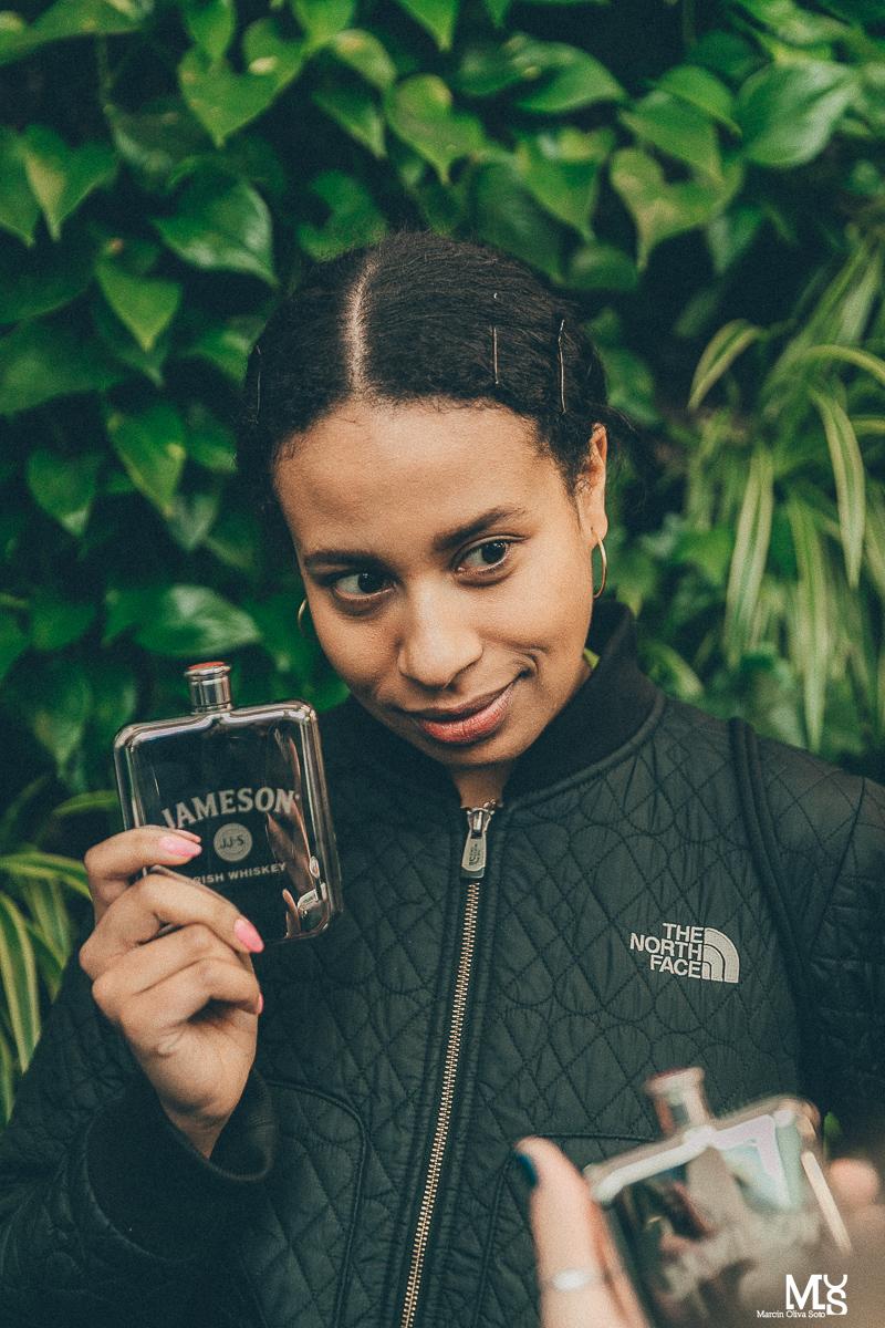 Kobieta o ciemnej karnacji w czarnej kurtce z piersiówką Jameson