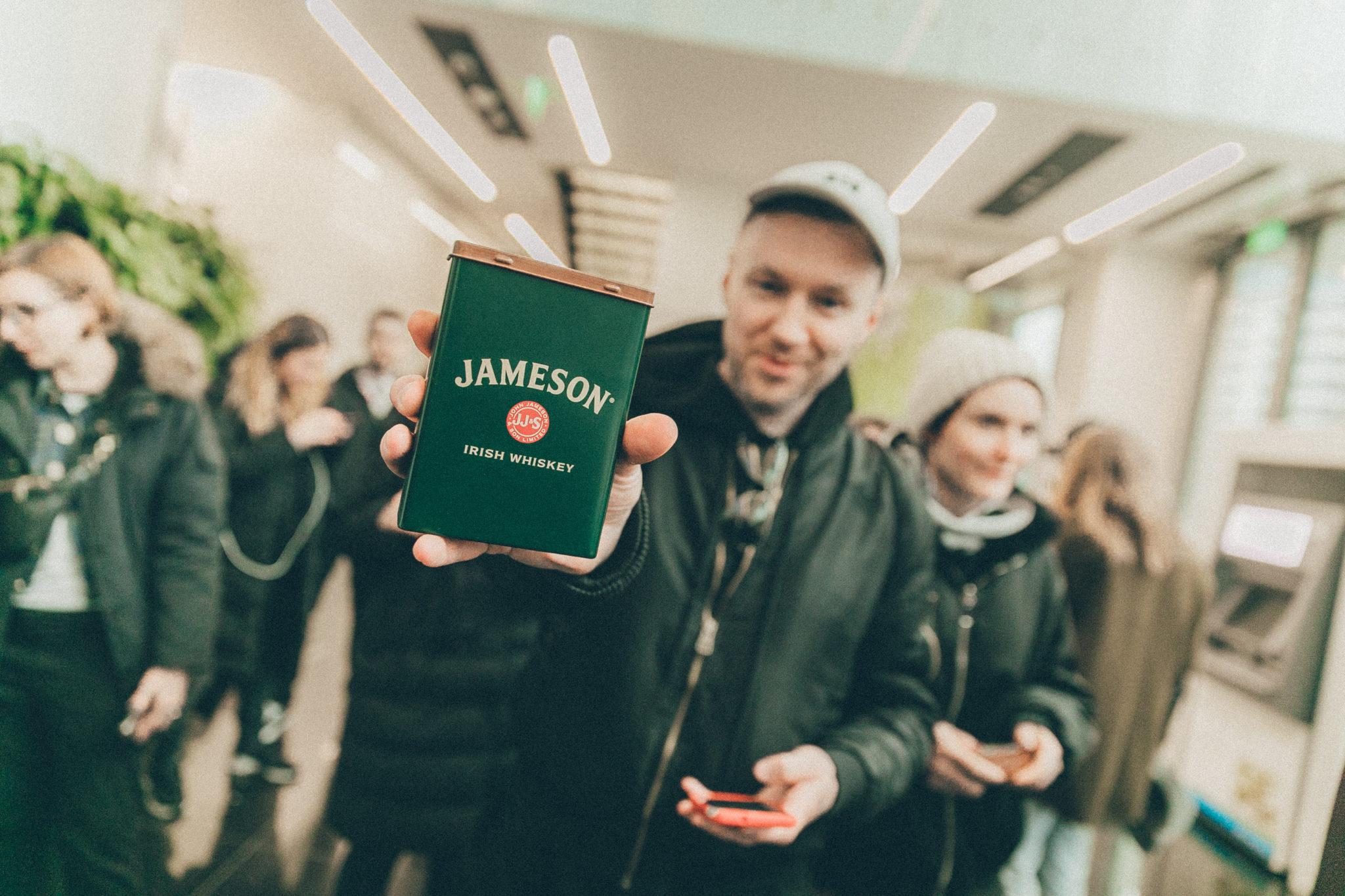 Mężczyzna w białej czapce trzymający puszkę Jameson