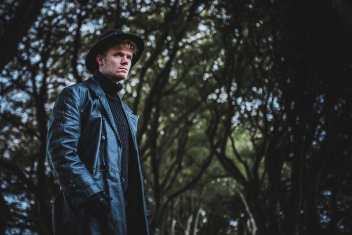 Mężczyzna w płaszczu i kapeluszu na środku lasu