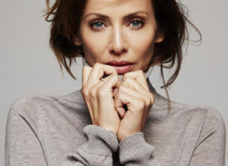 Na zdjeciu widzimy portret brunetki ubranej w bezowy sweter rece trzyma przy twarzy
