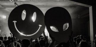 Tłum na koncercie i osoby trzymające uśmiechniętą buźkę i twarz ufoludka