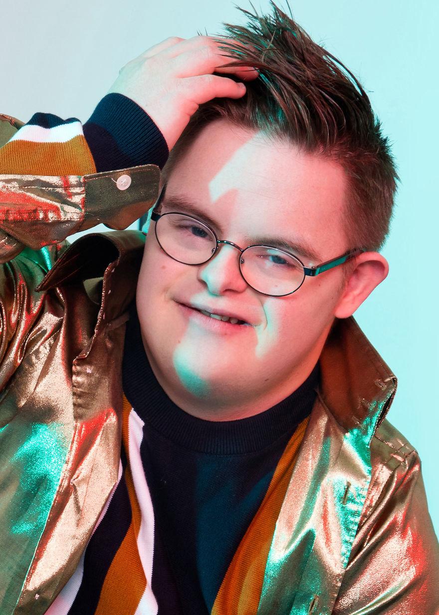 Chłopak w okularach i złotej kurtce trzymający się za głowę