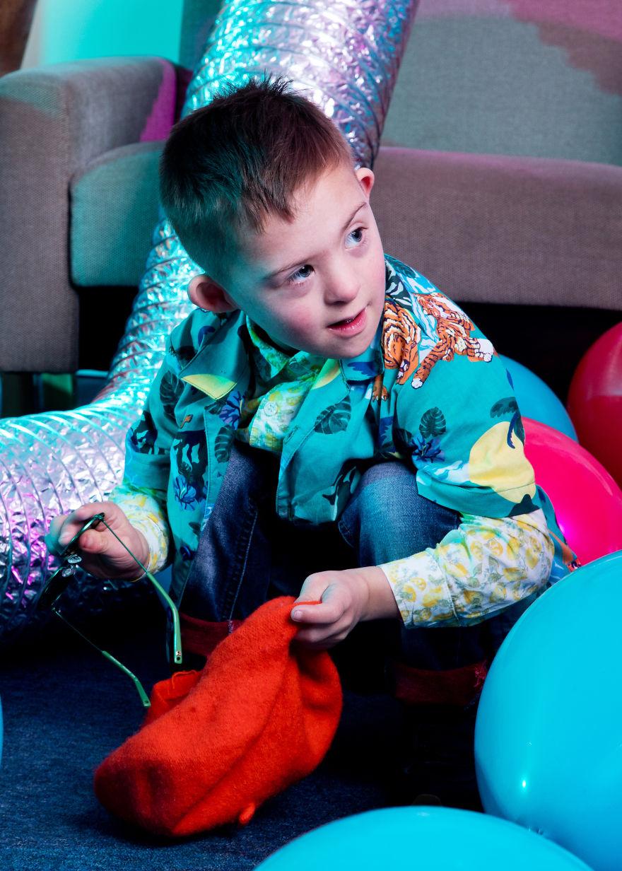 Chłopiec ubrany na kolorowo, patrzący w bok
