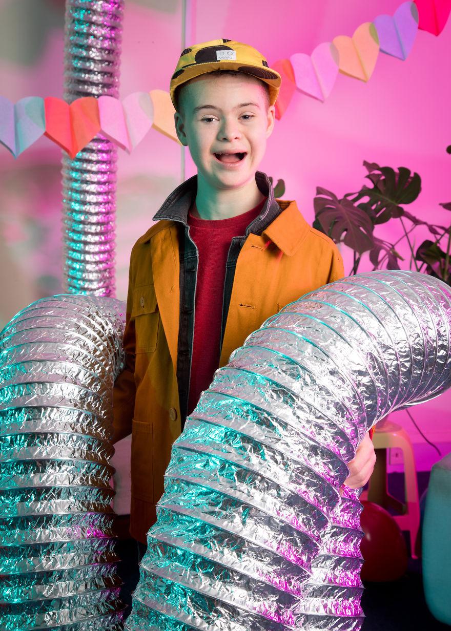 Śmiejący się chłopak ze srebrnymi rurami w dłoniach