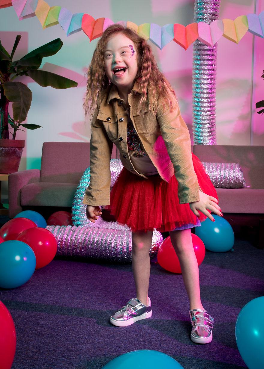 Śmiejąca się dziewczynka w czerwonej spódnicy i kurtce
