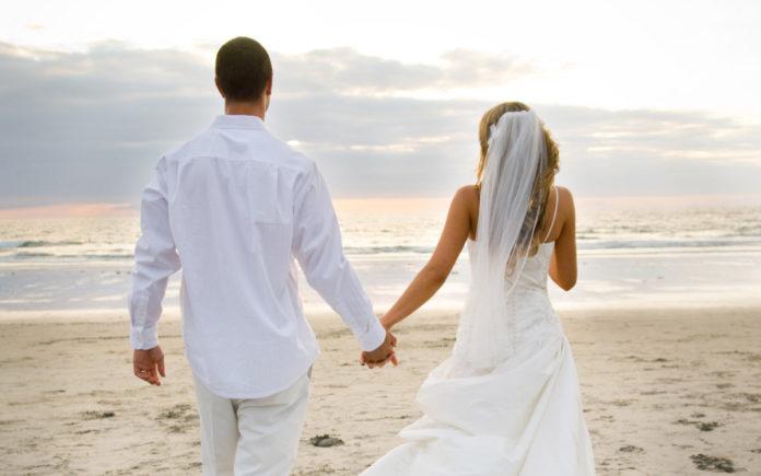Para nowożeńców spacerująca plażą