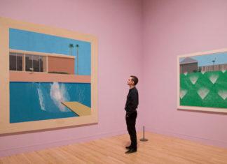 Człowiek ubrany na czarno oglądający obraz na różowej ścianie